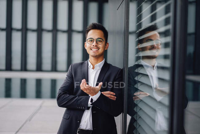 Smiling handsome man looking at camera and gesturing with hands — Stock Photo