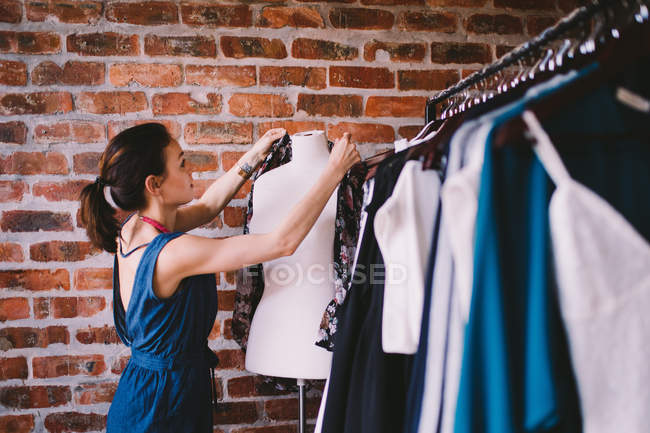 Fashion designer hanging blouse on mannequin in showroom — Stock Photo