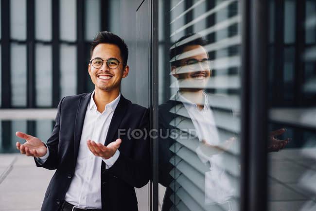 Sonriendo apuesto mezclado a hombre carrera mirando a cámara y gesticulando con las manos - foto de stock