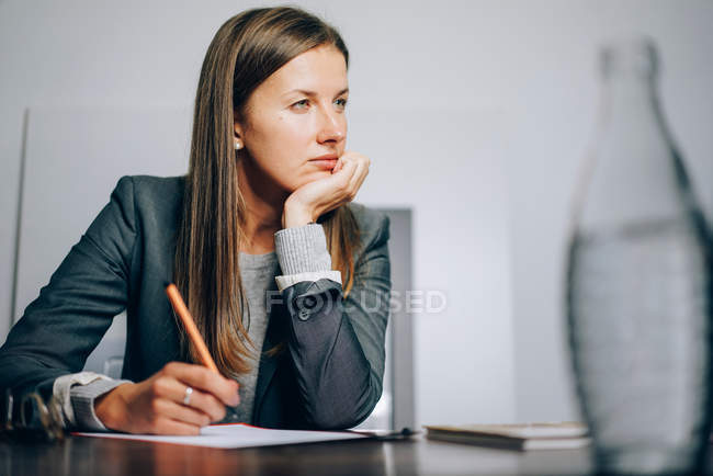 Thinking woman sitting at her desk with pen and paper — Stock Photo