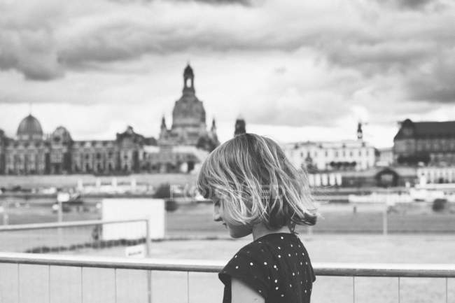 Pretty young girl standing on balcony overlooking the city — Stock Photo