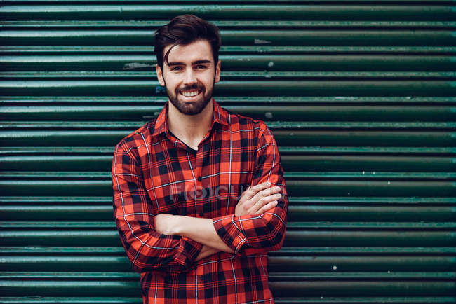 Portrait of young man standing against wall and smiling with crossed arms — Stock Photo