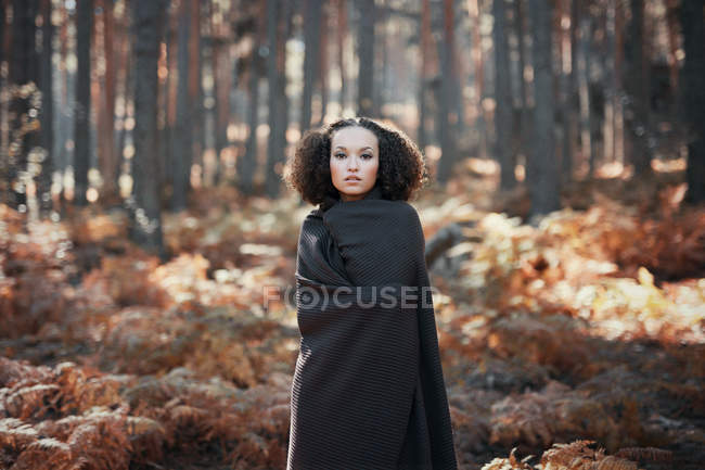 Portrait of a young woman in forest during autumn season — стоковое фото