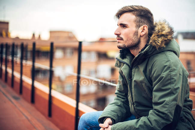 Fashionable young man in green parka jacket posing outdoors — Stock Photo