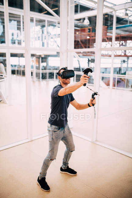 Full length of young man playing games with virtual reality headset — Stock Photo