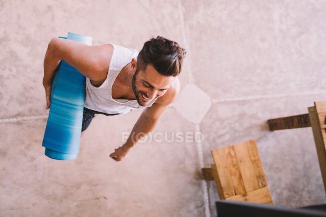 Aerial view of young man holding yoga mat — Stock Photo