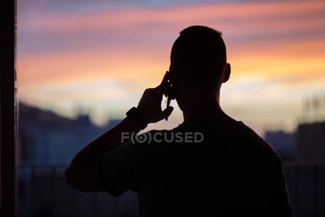 Silhouette de jeune homme au téléphone contre le coucher de soleil — Photo de stock