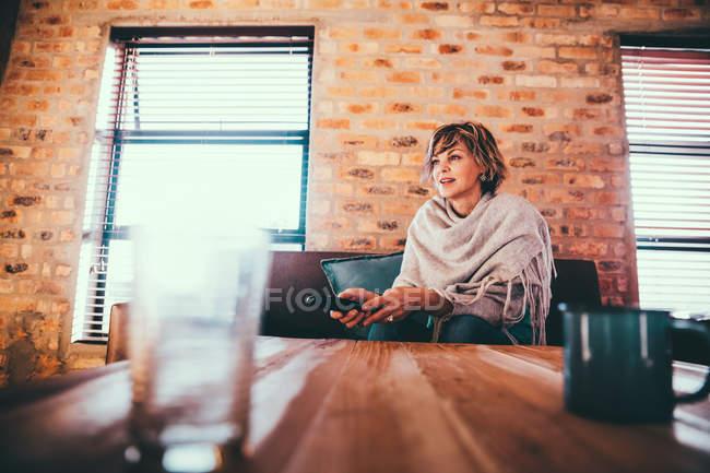 Mujer madura viendo Tv en casa y sentados en el sofá - foto de stock