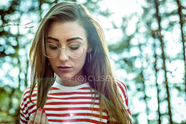 Stylish hipster girl wearing red striped top and touching hair — Stock Photo