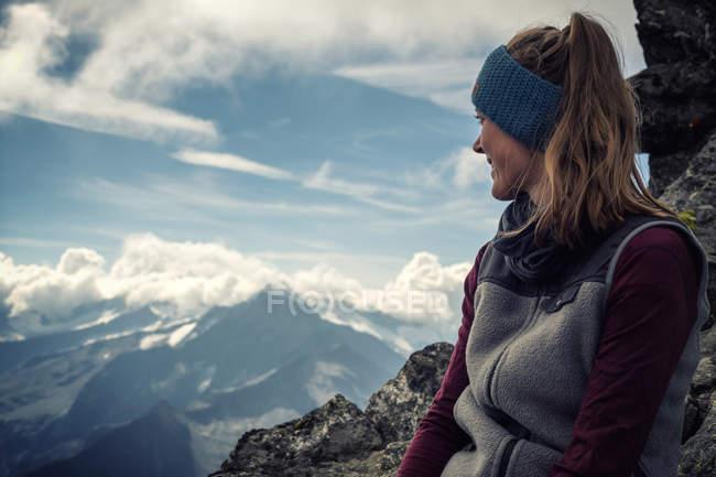 Sourire de crête de montagnes aux sommets enneigés surplombant femme — Photo de stock