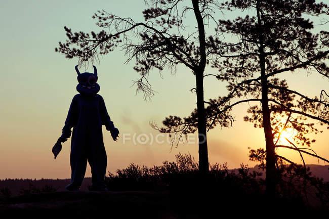 Persona che indossa costume mostro e in piedi nelle montagne al tramonto con l'ascia — Foto stock