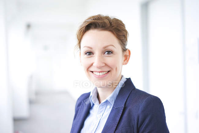 Portrait of smiling business woman looking at camera and wearing blue suit jacket — Stock Photo