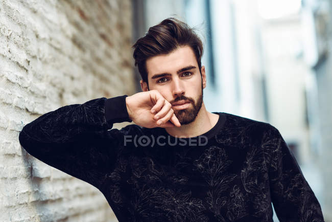 Portrait of handsome man looking at camera and leaning on brick wall — Stock Photo
