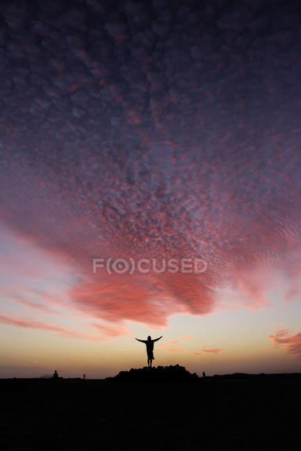 Homme silhouette adossé rose ciel au coucher du soleil — Photo de stock