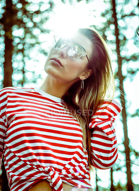 Stylish hipster girl wearing red striped top and posing in sunglasses — Stock Photo