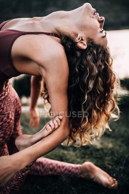 Young woman doing flexible yoga exercise outside — Stock Photo