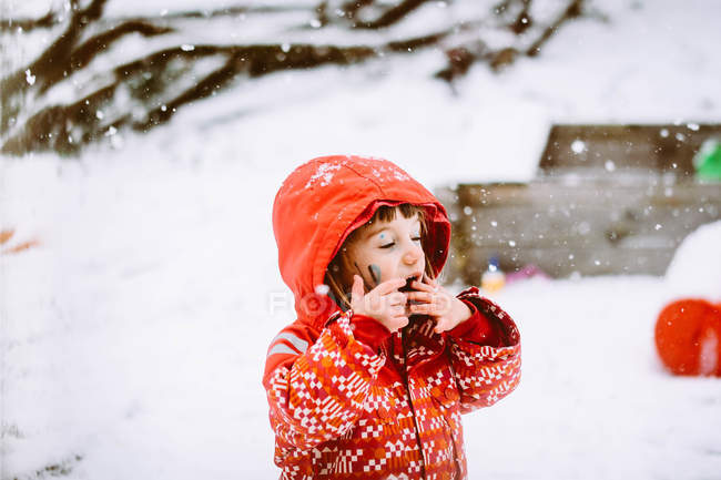 Close-up of smiling girl in snow catching snowflakes — Stock Photo