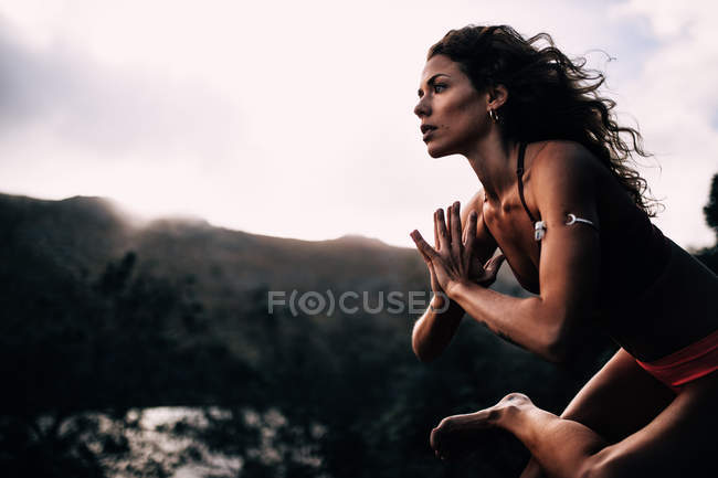 Side view of young woman practicing yoga against mountain — Stock Photo
