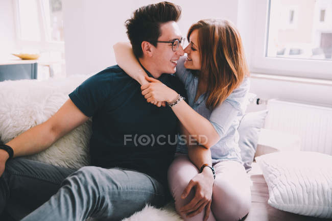 Loving couple enjoying time together and embracing on sofa at home — Stock Photo