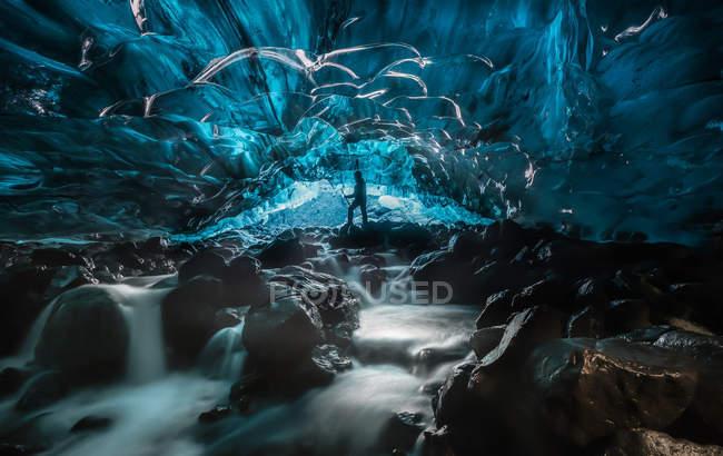 Вода течет внутри ледника замороженных пещере, силуэт человека в пещере — стоковое фото