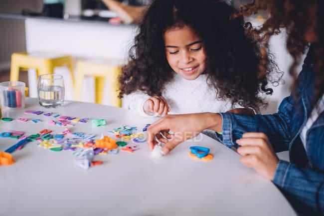 Bambina che gioca con i giocattoli di argilla a casa — Foto stock