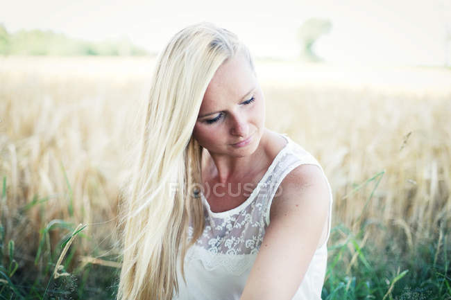 Portrait of beautiful blonde woman in field — Stock Photo