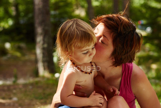 Mother kissing small daughter in park — Stock Photo