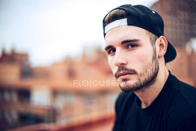 Handsome young caucasian man in black cap  looking at camera — Stock Photo