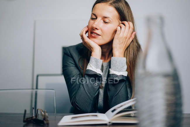 Business woman sitting at her desk with book and glasses — Stock Photo