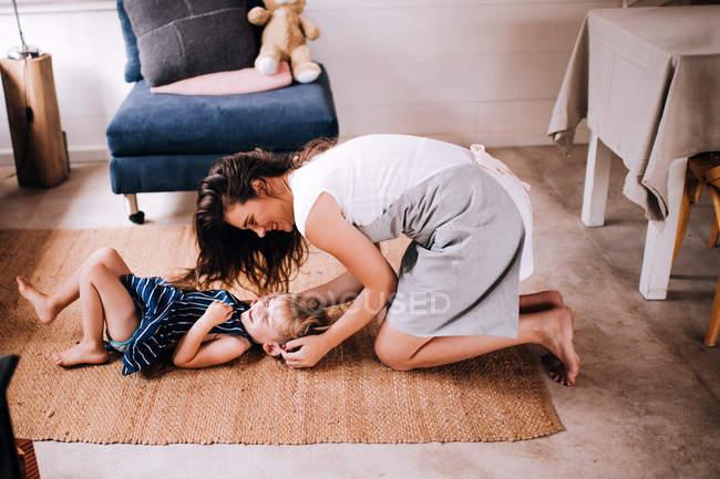 Ragazzino sveglio e sua madre che gioca sul tappeto a casa in camera — Foto stock