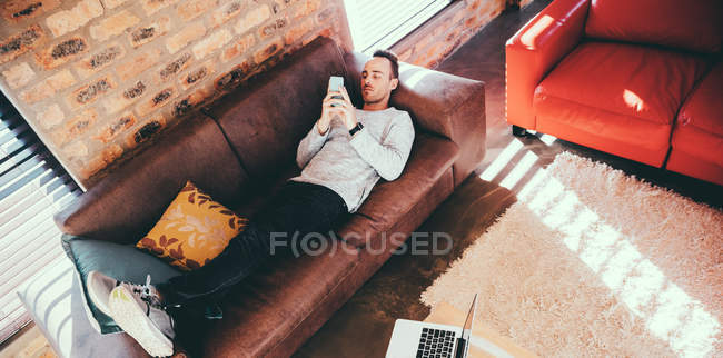 Young adult man laying on couch browsing his smartphone, high angle view — Stock Photo
