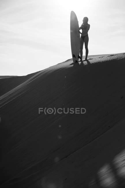 Femme de silhouette debout avec planche de surf — Photo de stock