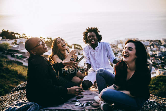 Young group of people sitting together on city hill — Stock Photo