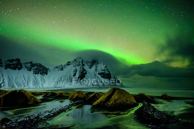 Scenic view on snow covered mountains under a green sky at night with aurora borealis lights - foto de stock
