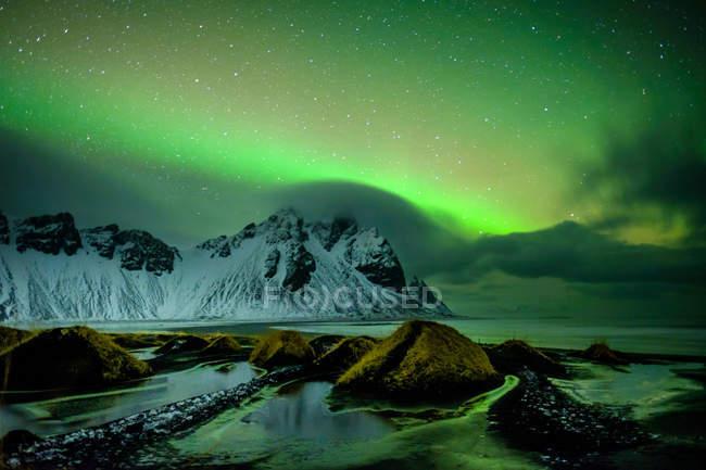 Живописный вид на снегу покрыты горы под зеленым небо ночью огнями северное сияние — стоковое фото