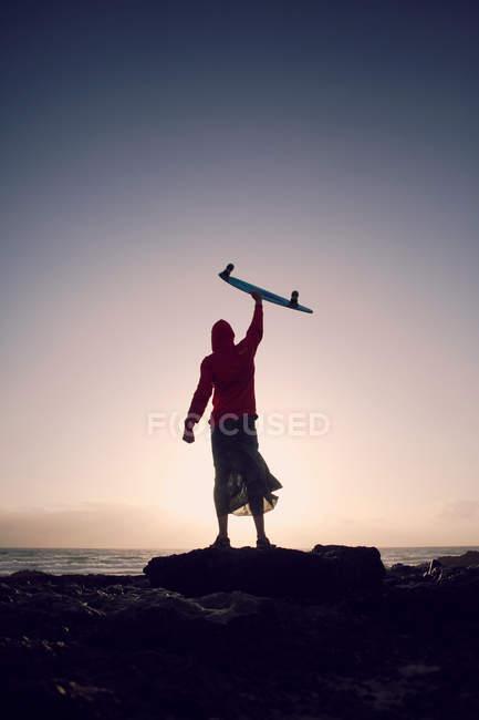 Toute la longueur de l'homme silhouette debout sur la plage dans le ciel — Photo de stock
