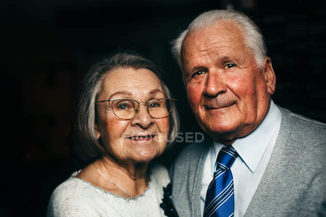 Elderly couple in love, pensioners embracing and looking at camera — Stock Photo