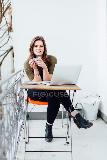 Young woman drinking cup of tea while sitting with  laptop — Stock Photo