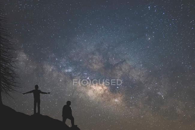 Silhouette de deux personnes debout sous le ciel étoilé — Photo de stock