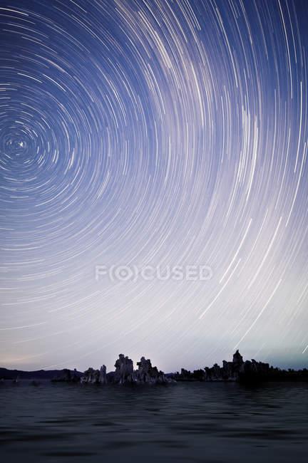 Tir longue exposition de mer sous le ciel étoilé, star trail — Photo de stock