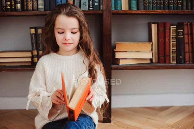 Beautiful young girl reading book and sitting on floor at book shelves — Stock Photo