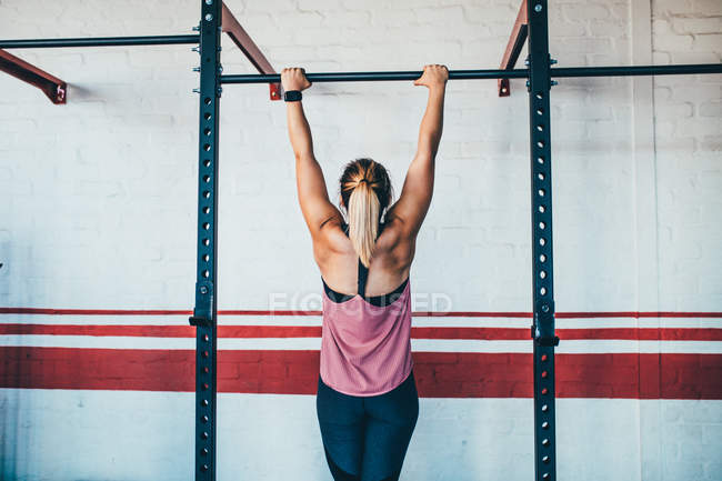 Strong female athlete doing pull up in gym — Stock Photo