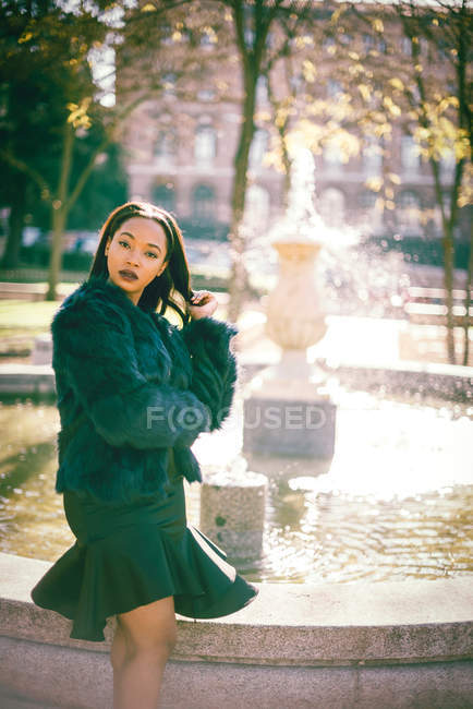 Fashionable gorgeous African woman in fur coat outdoors in park at fountain — Stock Photo