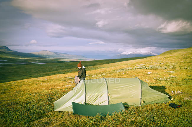 Hiker camping in meadow in mountains — Stock Photo