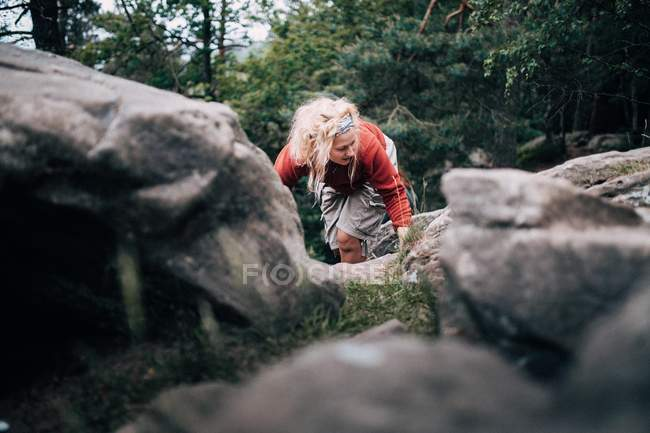 Young woman hiking up mountain with rocks — Stock Photo