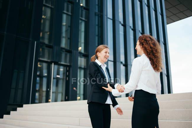 Два деловых женщин чате вне в офисное здание — стоковое фото