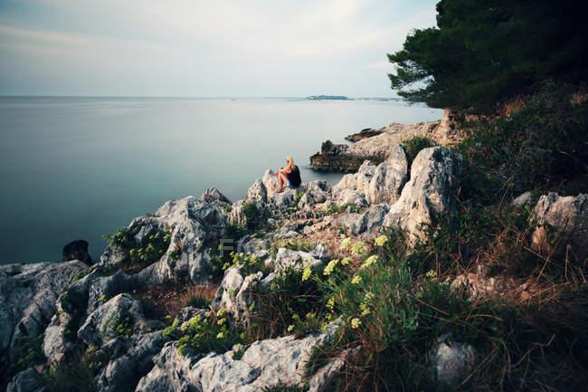 Joven mujer sentada sobre las rocas en el exterior tranquilo en la naturaleza - foto de stock