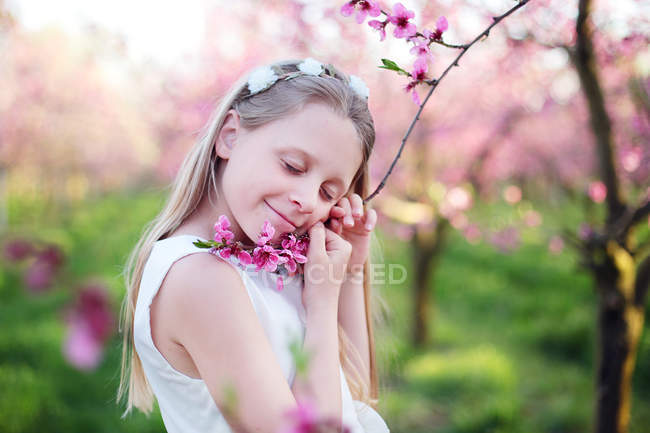 Blonde young girl holding pink flowering tree branch — Stock Photo
