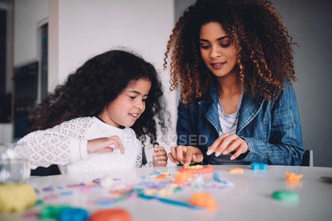 African mother and daughter playing with modelling clay toys at table at home — Stock Photo