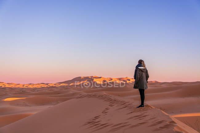 Vista posteriore della donna in piedi sulla duna di sabbia al tramonto — Foto stock